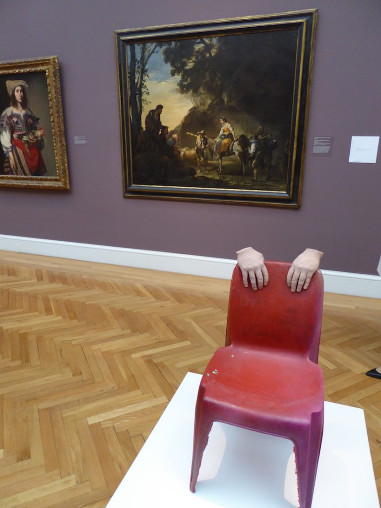 The hands on a chair sculpture inspired by Urs Fischer in the Legion of Honor San Francisco