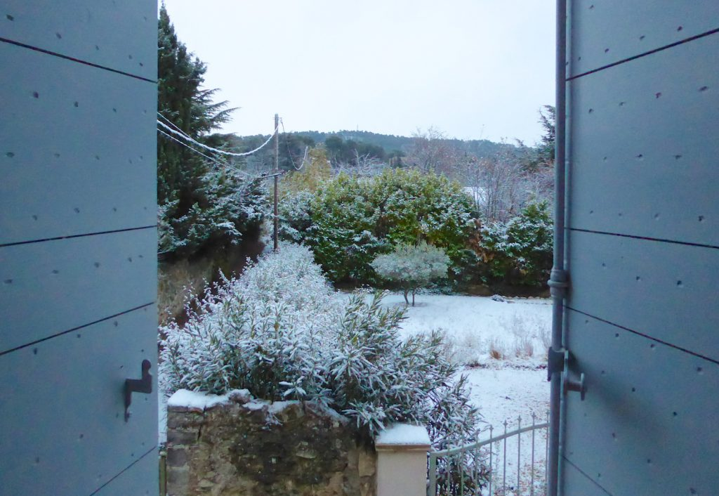 Opeing the xhutters after snowfall in Lourmarin, Luberon, Provence, France