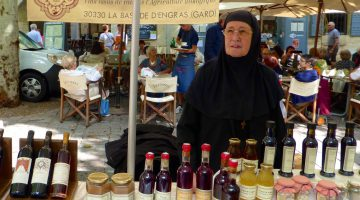 Nun selling wine at Wednesday Market in Uzes, Languedoc Roussillon, France