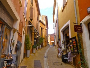 A Rousillon street full of the orche coloured buildings, from the local area