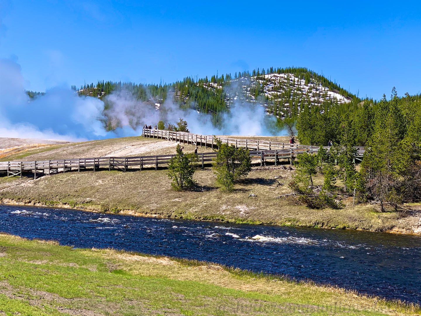The steaming Midway Geyser Basin, by The Firehole River at Yellowstone National Park